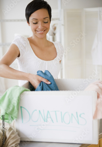 Mixed race woman putting clothing in donation box