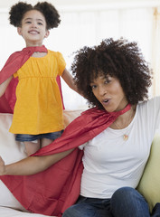 Mother and daughter wearing superhero capes