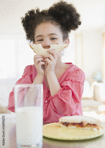 Mixed race girl holding sandwich in front of face