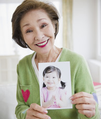 Japanese woman holding photograph of girl