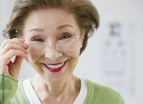 Japanese woman holding eyeglasses