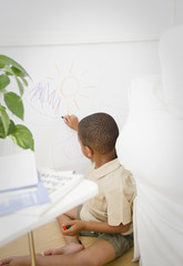 African American boy drawing on wall with crayon