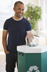 Mixed race man putting plastic bottle in recycling bin