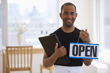 Mixed race waiter in restaurant holding menu and open sign
