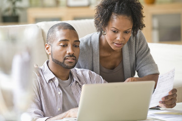 Black couple paying bills using laptop