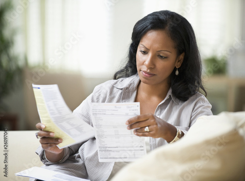 Hispanic woman sitting on sofa reading bills