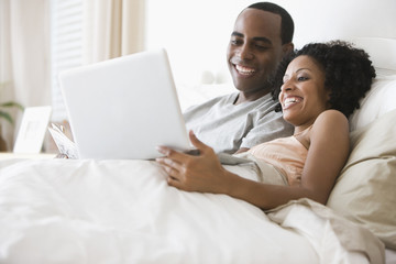 Couple laying in bed using laptop