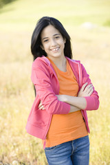 Hispanic girl in field with arms crossed
