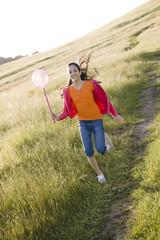 Hispanic girl running in field with net