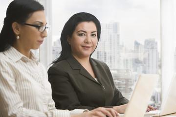 Businesswomen using laptops