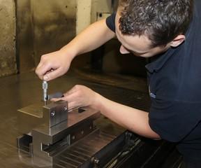 Werkzeugmacher-Azubi beim Messen mit Mikrometer