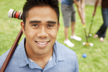 Smiling man holding croquet mallet