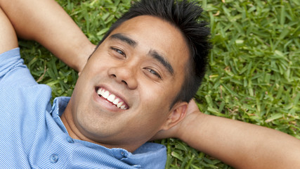 Smiling man laying in grass
