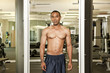 African American man with bare chest posing in health club