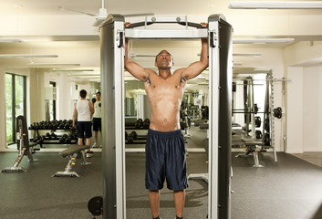 African American man with bare chest and arms raised in health club
