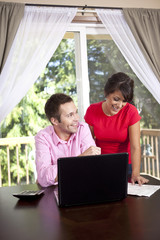 Couple paying bills and using laptop