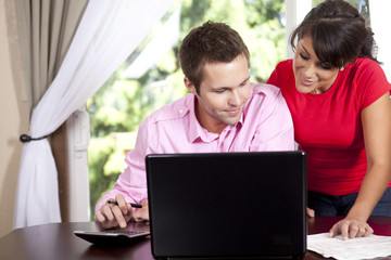 Couple paying bills and using laptop and calculator
