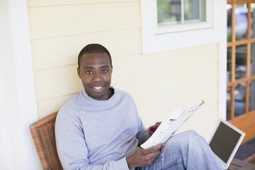 Black man on porch reading magazine