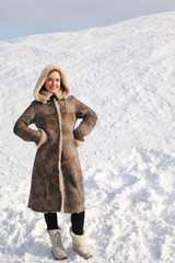 woman in long coat standing on snowy area and smiling