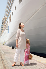mother and daughter standing in dock near cruise liner