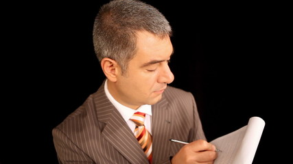 Businessman writing on notepad, black background