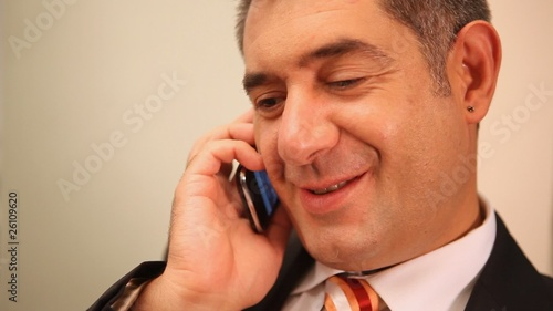 Businessman using mobile phone, smiling, chatting