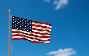 Flag of the USA waving in the wind in front of blue sky
