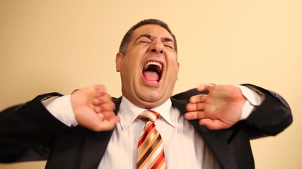 Tired businessman yawning and stretching - Exhausted