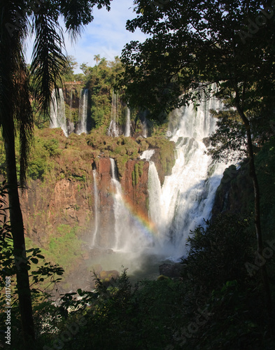 Igaucu falls through trees with rainbow and rocks