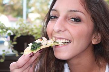 Eine junge Frau isst ein leckeres Stück Pizza