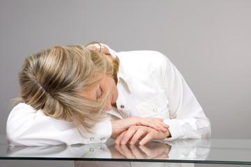 Senior woman sleeping on the table