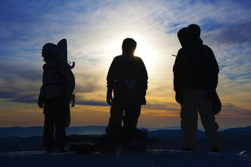Silhouettes of the three backcountry freeriders in evening