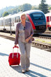 Ältere Seniren Frau am Bahnhof. Reisen in den Urlaub