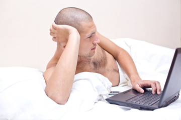 A man lying in bed looking at his laptop