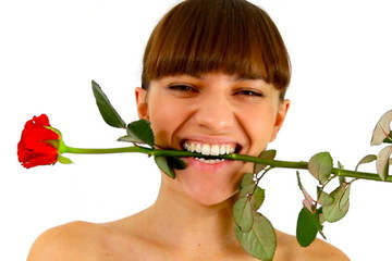 Attractive woman holding a rose in her mouth, isolated