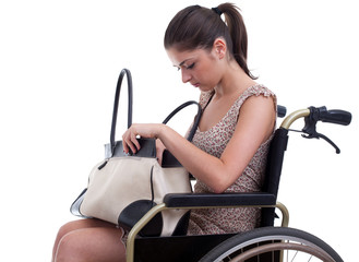 young invalid woman with bag on the wheelchair