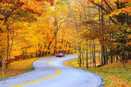 Car on curvy road in autumn with motion blur to show speed
