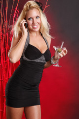 Cute blond in cocktail dress on a call while having a martini