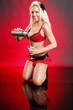 Cute blond in red bikini serves a martini on red
