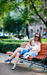 Mother and son on bench in park
