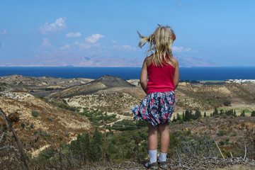 girl looks at the beautiful sea, beach and mountains in Greece