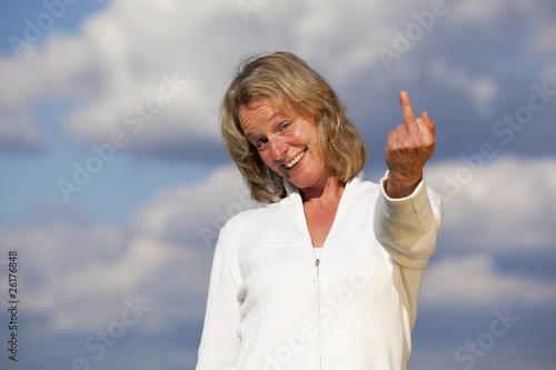 lächelnde hübsche blonde Frau zeigt Mittelfinger