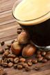 kaffeebohnen und haselnüsse neben glas mit espresso