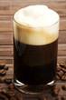 espresso mit milchschaum und kaffeebohnen