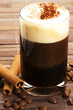 espresso mit milchschaum schokopulver zimtstangen kaffeebohnen