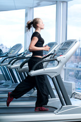 Young woman at the gym. Run on a machine