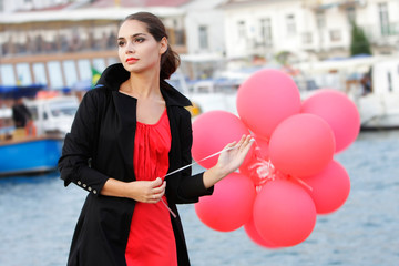 outdoor portrait of young beautiful woman with red balloons
