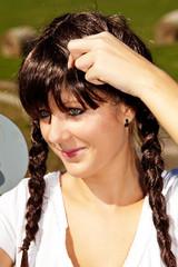 Junge Frau mit Perücke schaut in Spiegel 906