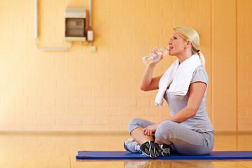 Durstige Frau im Fitnesscenter