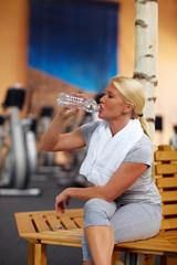 Frau im Fitnesscenter trinkt Wasser